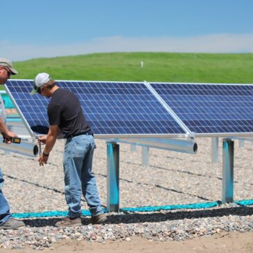 Two men measure and install a solar panel